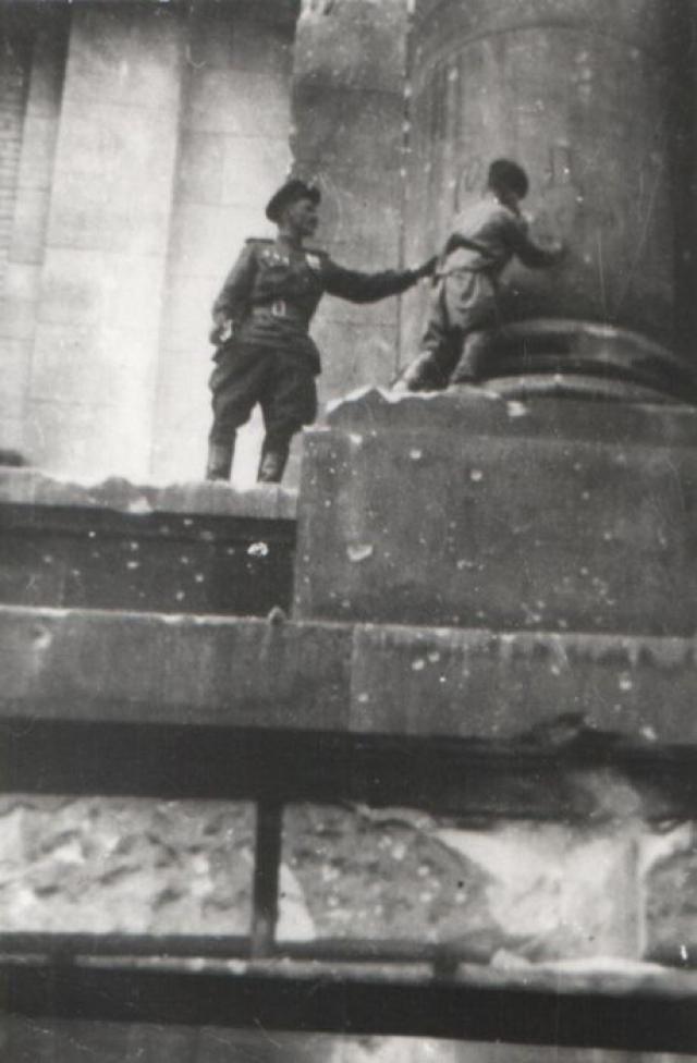 Сын полка Володя Тарновский ставит автограф на колонне Рейхстага.