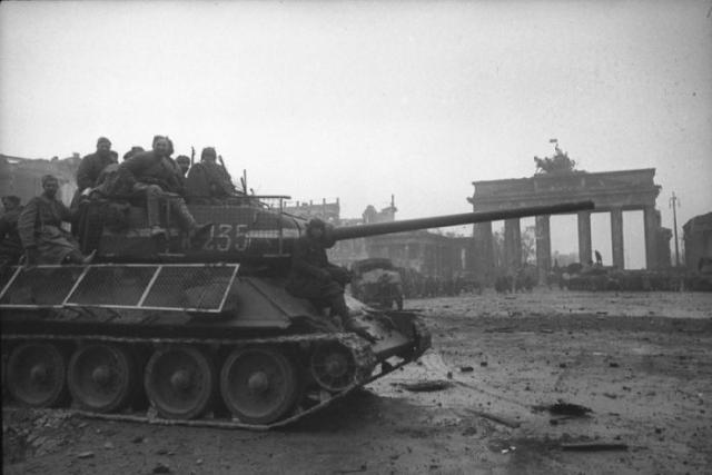 """Советские солдаты на Т-34-85 на фоне Бранденбургских ворот в Берлине. Танк закрыт сетчатыми экранами, защищавшими от попаданий из """"фаустпатронов""""."""