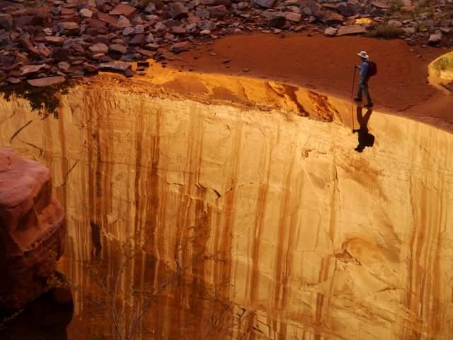 Обрыв - или река? Создается ощущение, будто мужчина движется по краю обрыва, но на самом деле его путь пролегает по берегу реки, находящейся внутри Глен-Каньона в Национальном парке США.