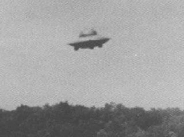 """Вунсокет, штат Род Айленд, 1967 Гарольду Труделю удалось сделать несколько снимков в районе Восточного Вунсокета в США. На фотографиях можно разглядеть купол на дискообразном объекте слегка асимметричной формы. Трудись утверждал, что НЛО передвигался очень быстро. Очевидец наблюдал за """"тарелкой"""" в течение пяти минут, пока та не устремилась на север. Возможное объяснение: не ископчено, что очевидец сам сконструировал """"НЛО"""" и каким-то образом запустил его в небо."""