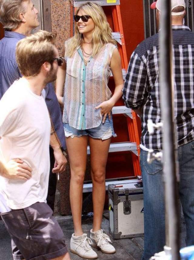 """Кейт Аптон на сьемке сцены для фильма """"Другая женщина"""" в китайском квартале, Нью Йорк, 24 июня, 2013 года. Супермодели Кейт уже наложили грим, она улыбается и ходит по площадке в коротких шортах."""