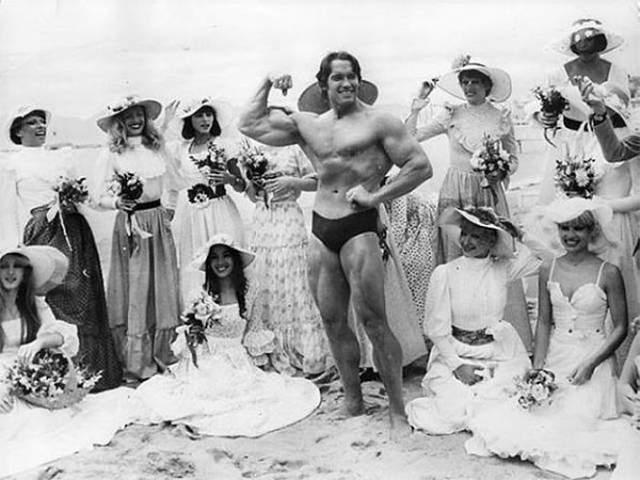 """Арнольд Шварценеггер позирует на пляже вместе с танцовщицами парижского кабаре """"Фоли-Бержер"""". Канны, 1977-й год."""