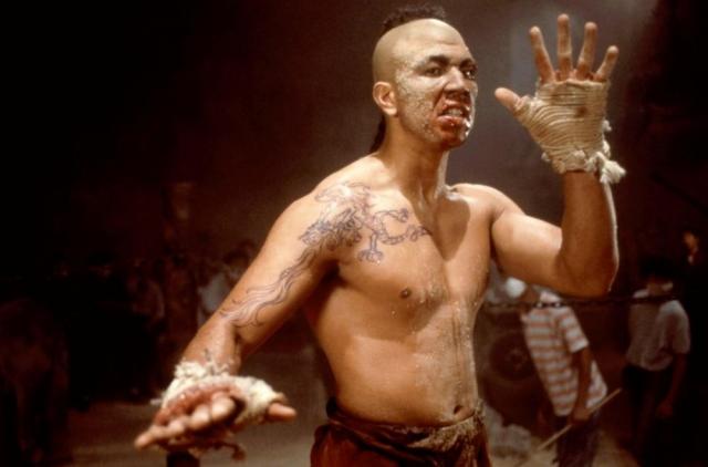 """Мишель Кисси. Актер запомнился зрителям ролью здорового тайского боксера Тонг По, который разделывается с братом Ван Дамма в фильме """"Кикбоксер"""" и лупит ногой в каменную колонну на тренировке. Дружба с Ван Даммом стала определяющей в судьбе марроканца Кисси. Марокканец появлялся в титрах, пожалуй, каждого фильма бельгийца, как актер, тренер, каскадер или хореограф."""