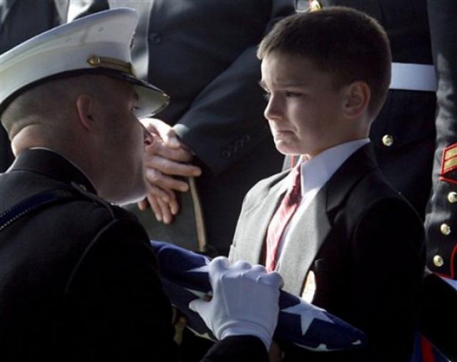 Восьмилетний Кристиан принимает флаг во время поминальной службы по его отцу, который был убит в Ираке всего за несколько недель до того, как он был должен возвратиться домой.