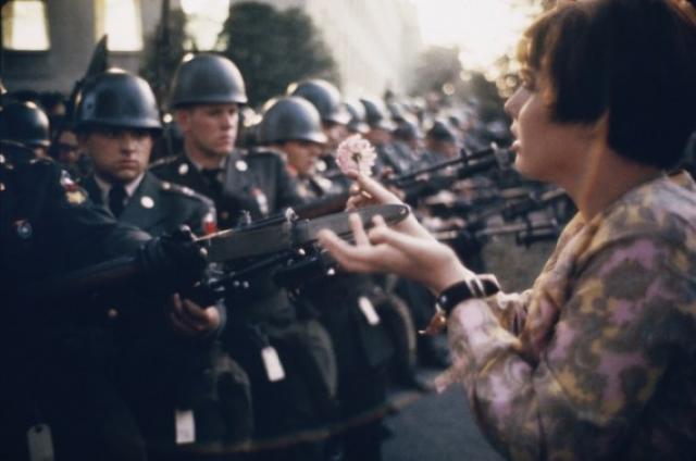 Молодой пацифист Джейн Роуз Кэсмир, с цветком на штыках охранников в Пентагоне. Во время протеста против войны во Вьетнаме. 1967 год.