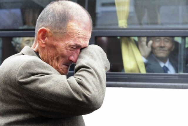 Человек из Северной Кореи (справа) машет рукой из автобуса плачущему южнокорейцу после семейной встречи у горы Кумганг, 31 октября 2010 года. Их разлучила война 1950-53 годов.