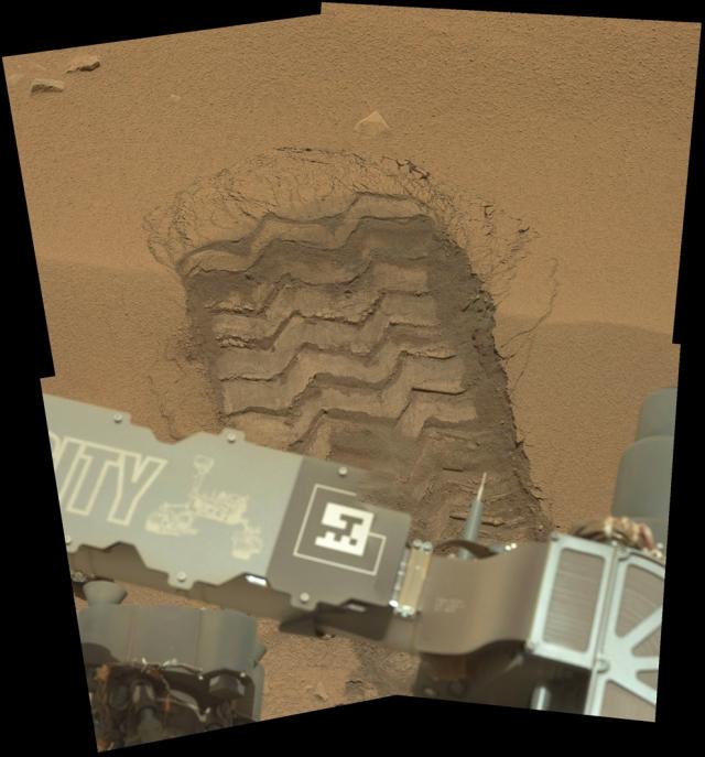 След от колеса марсохода на песке Марса.
