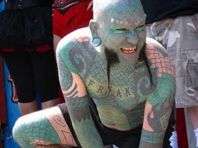 700 часов татуирования, 5 тефлоновых роговых отростков на бровях, зубы, превращенные в клыки, разрез на языке и тоннели в ушах - вот комплект манипуляций, превративших Эрика в ящера.