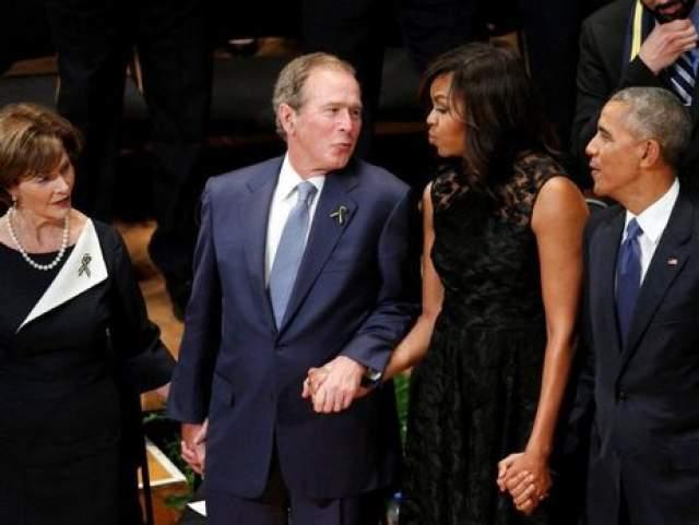 """Буш уже не был президентом, но стоял рядом с ним, держа за руку супругу Обамы Мишель. На тот момент 70-летний политик улыбался, напевая """"Аллилуйя"""", сначала просто покачивался, а затем начал в ритм двигать руками. Первая леди попыталась унять диско-боя, но тот не понял настроя окружающих."""
