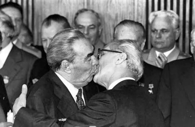 """Поцелуй Брежнева с руководителем ГДР Эриком Хонекером был изображен художником Дмитрием Врубелем на Берлинской стене в 1990 году. Работу художник назвал """"Господи! Помоги мне выжить среди этой смертной любви""""."""
