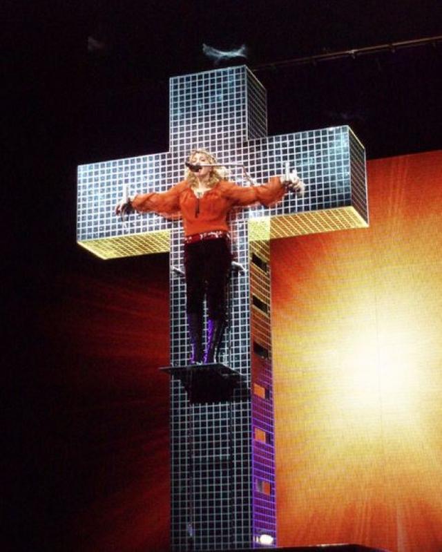 """На концерте в Лос-Анджелесе Мадонна приковала себя к огромному зеркальному кресту, надела на голову """"терновый венец"""" и исполнила балладу Live To Tell. По слухам, декорации обошлись певице в 8 миллионов долларов."""