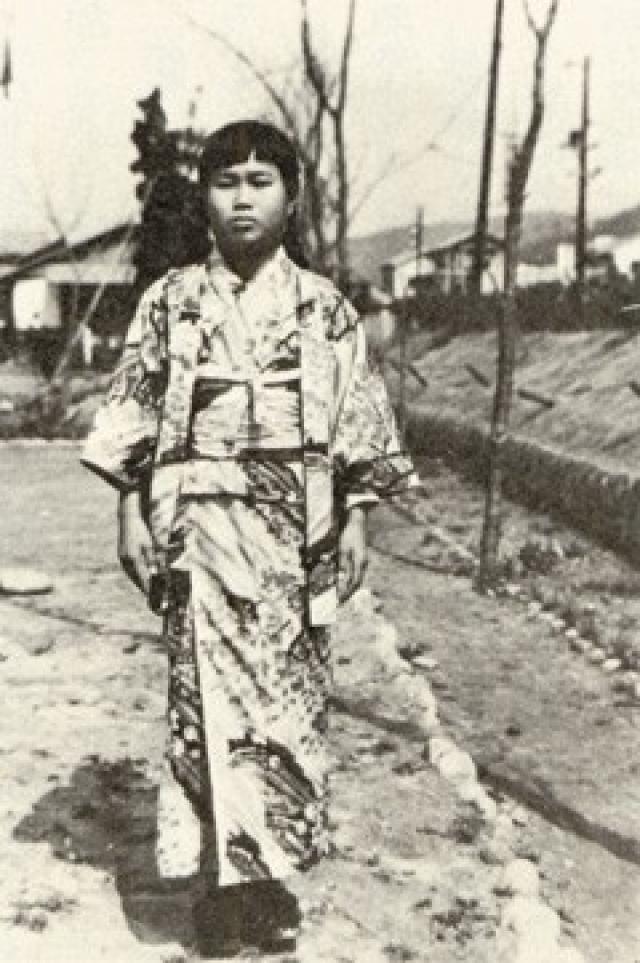 Взрывная волна вынесла ее через окно, но девочка осталась жива. В ноябре 1954 у нее проявились первые признаки болезни - на шее и позади ушей проявилась опухоль.