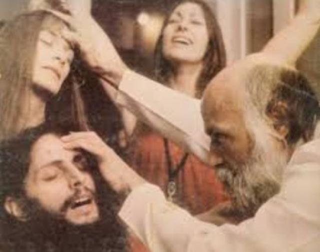 """Секта Бхагавана Шри Раджниша (Ошо). В 1966 г. Раджниш покинул университет и начал проповедовать собственное учение, которое являло собой парадоксальную смесь из огрызков джайнизма, тантризма, дзэн-буддизма, даосизма, суфизма, хасидизма, ницшеанства, психоанализа, популярных """"психо-духовных"""" терапий и учений Кришнамурти и Гурджиева."""
