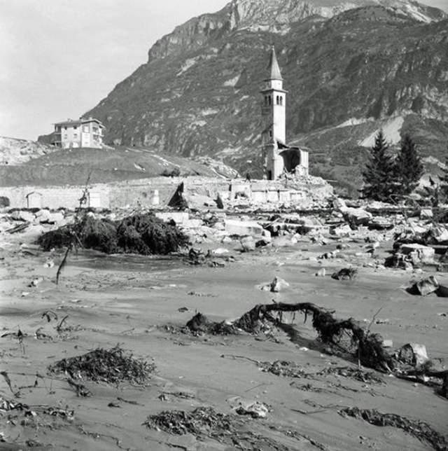 """Над """"лунным пейзажем"""" из грязи, камней и обломков бывшего города остались стоять лишь несколько зданий, которым повезло находиться на небольшом холме, да одинокая колокольня приходской церкви. Сама церковь была полностью разрушена ."""