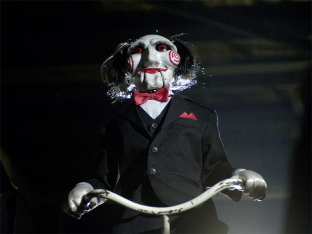 """""""Пила"""" . В маске предстает зловещий маньяк по прозвищу """"Конструктор"""", которое он получил из-за того, что на теле своих жертв он вырезал кусочек кожи, похожий на элемент мозаики в игре """"Пазл""""."""