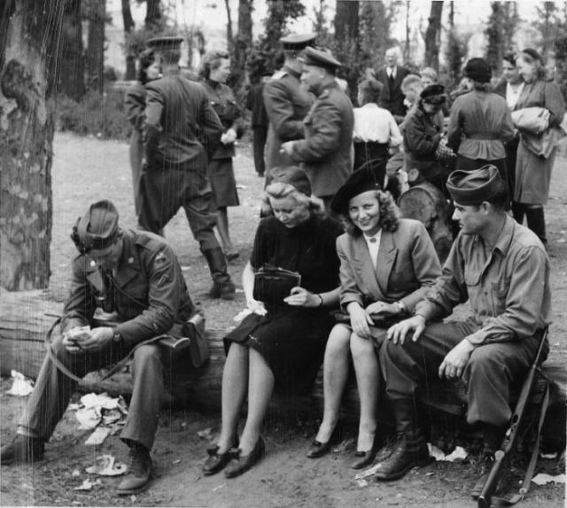 Американские солдаты, пришедшие в берлинский сад Тиргартен для обмена наручных часов, общаются с немецкими девушками. На заднем плане группа советских военнослужащих.