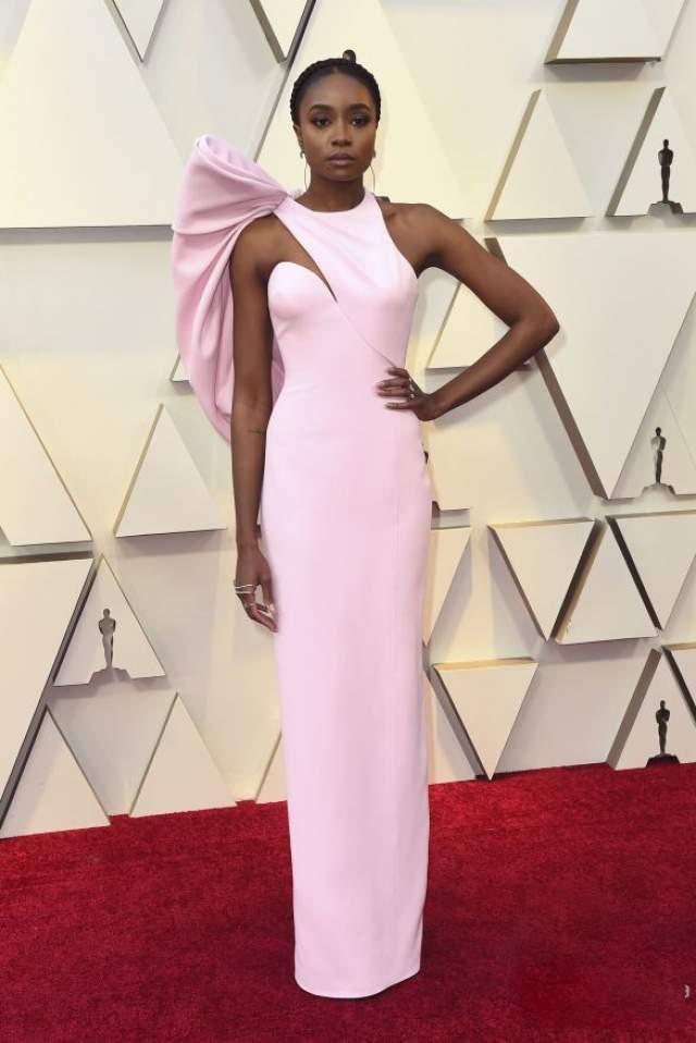 """Кики Лэйн в Atelier Versace. На красной дорожке в 2019 году было действительно много розового, причем на разный вкус и цвет, но сыгравшая главную героиню из """"Если Бил-стрит могла бы заговорить"""" (Реджина Кинг из него взяла премию как лучшая актриса второго плана) девушка выбрала, считают самые стильные мира сего, наиудачнейший оттенок."""