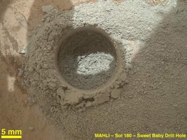 Марсоход Curiousity просверлил отверстие в поверхности Марса, чтобы взять образцы грунта, 4 февраля 2013 года. Диаметр отверстия - около 1,6 см.