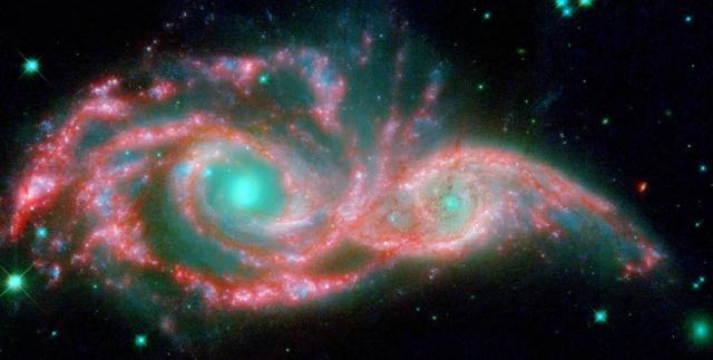 """""""Глаза"""" в небе. Это изображение галактик, принявших форму гигантской маски, было получено на основании съемок телескопов """"Хаббл"""" и """"Спитцер"""". Эти голубые """"глаза"""" на самом деле ядра двух сливающихся галактик, обозначенных номерами NGC 2207 и IC 2163"""