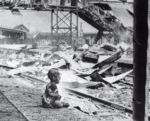 Кровавая суббота, С. Х. Вонг, 1937. В тот день японские ВВС налетели на шанхайский городской вокзал. На снимке - ребенок, которого спасатель вынес из разрушенного вокзала и посадил на перроне, чтобы вернуться за остальными людьми.
