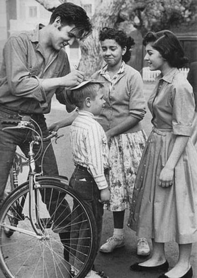 Элвис Пресли дает автограф на голове мальчика
