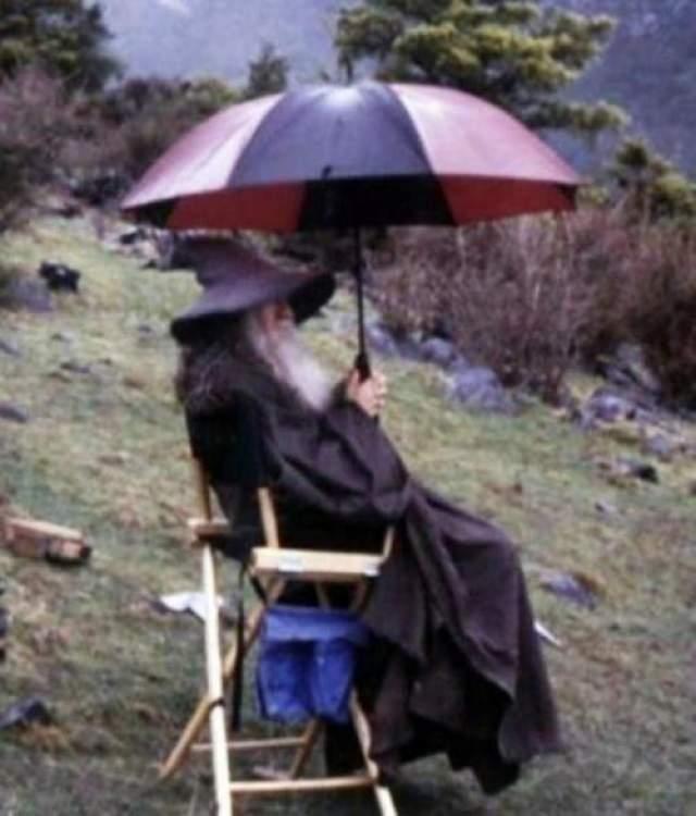 Трилогия Властелин Колец Гэндальф (Сэр Иэн Мюррей Маккелен) с зонтиком в перерыве между дублями.