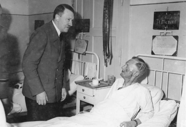 При взрыве бомбы погибли 4 человека, Гитлер остался жив, однако пострадал (на фото он навещает одного из офицеров, также как и он, пострадавшего в результате этого покушения).