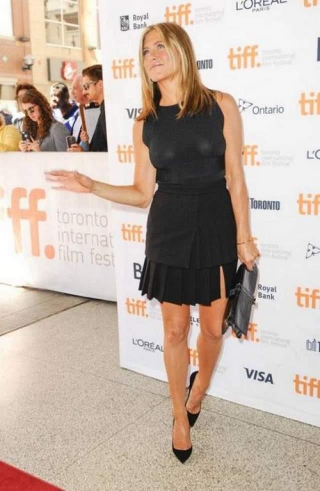 """Для премьеры фильма """"Пирог"""" Дженнифер Энистон выбрала консервативный черный топ Valentino и юбку Emanuel Ungaro, однако конфуза избежать не удалось - предательские фотовспышки высветили отсутствие бюстгальтера и ничем не покрытую грудь актрисы."""