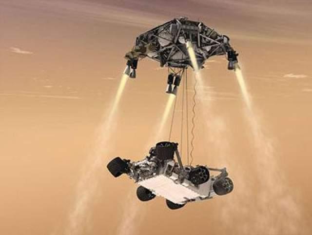"""""""Небесный кран""""- это специальный аппарат с ракетными двигателями. Огромный парашют и двигатели """"Небесного крана"""" замедлили падение до 3 км/час, после этого """"небесный кран"""" опустил марсоход на тросах на поверхность Марса. Curiousity был сразу поставлен точно на колеса, а тросы были автоматически обрезаны."""