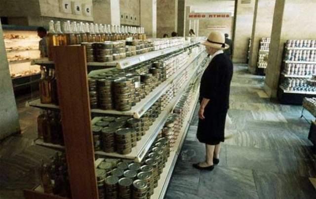 """Продуктовый отдел гастронома, 1972 год. Впечатление """"изобилия товаров"""" — это иллюзия. На полках всего 2-3 вида консервов и бутылки 0,7 с некой темной жидкостью — либо нерафинированным маслом, либо с алкоголем."""