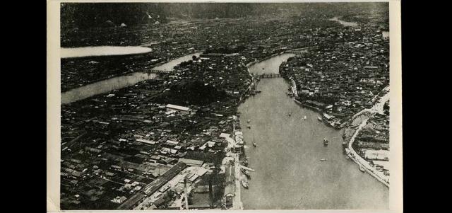 Вид на городок Хиросима с воздуха, снятый незадолго до того, как на город была сброшена бомба. Наф ото можно расмотреть густонаселенный район города, расположенный на реке Мотоясу.