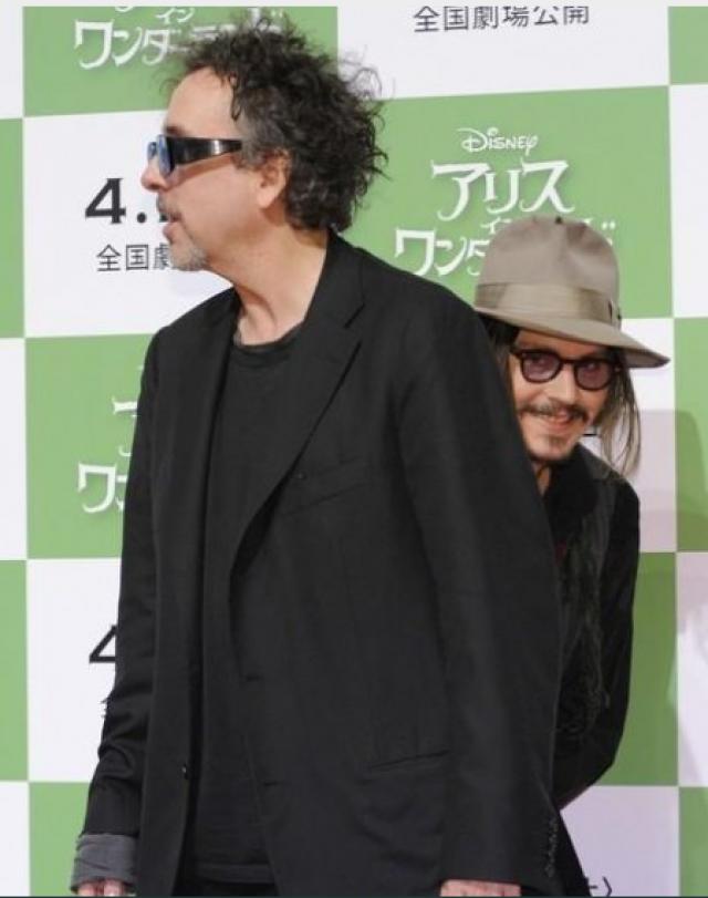 Джонни Депп кажется застенчивым перед японской толпой, когда прячется за спиной Тима Бертона.