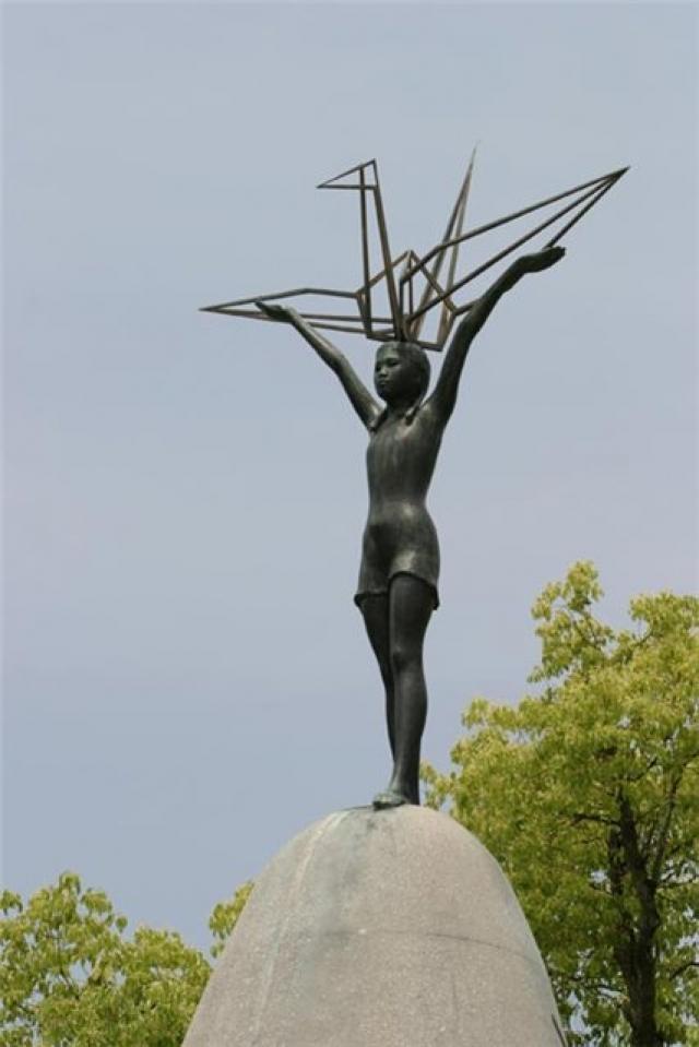 """Вдохновленные ее мужеством и силой воли, друзья и одноклассники Садако опубликовали ее письма. В 1959 году в Парке Мира в городе Хиросима была установлена статуя, изображающая Садако с бумажным журавликом в руке. На постаменте статуи написано: """"Это наш плач. Это наша молитва. Мир во всем мире""""."""