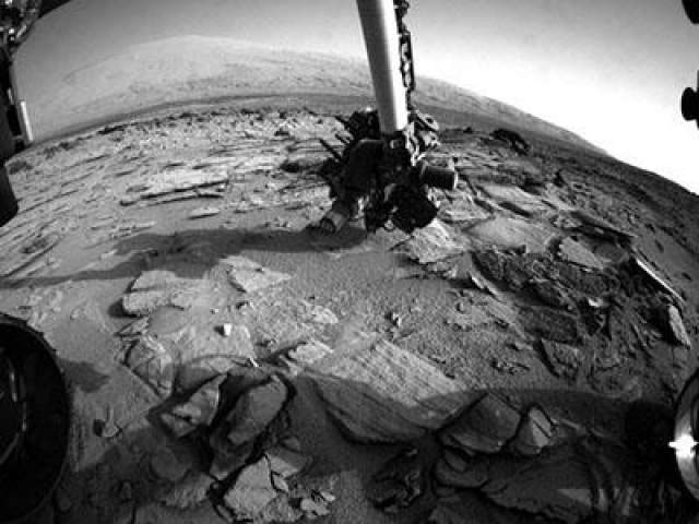 """Роботизированная """"рука"""" марсохода изучает горную породу и марсианский грунт, 3 июля 2013 года."""
