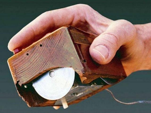 Приспособление представляло собой коробок из дерева с большими металлическими колесиками, красной кнопкой и шнуром, находящимся под запястьем пользователя.