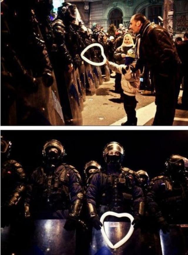 Румынский ребенок вручает воздушный шарик работнику полиции во время протестов в Бухаресте.