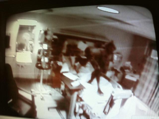 Это известное фото было снято медсестрой в неизвестной больнице с видеозаписи камеры наблюдения. Темная фигура стоит на пациенте, лежащем на кровати.
