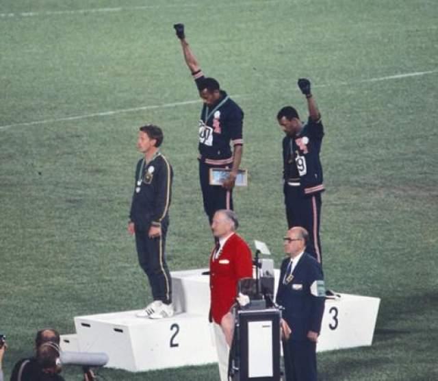 Медалисты в забеге на 200 метров Томми Смит и Джон Карлос - протест на пьедестале против расовой дискриминации Два чернокожих спортсмена, Томми Смит и Джон Карлос, завоевавшие для США золотую и бронзовую медали в беге на 200 метров на олимпиаде в Мехико, во время исполнения гимна США вместо того, чтобы смотреть на поднимающийся флаг своей страны, низко склонили головы, закрыли глаза и подняли вверх руки в черных перчатках. Оба стояли на помосте без обуви, только в черных носках, которые символизировали тяжелое положение чернокожего населения Соединенных Штатов.