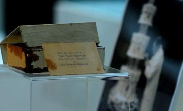 Кусок 68-летнего свадебного торта Елизаветы II и принца Филиппа. Он был упакован в оригинальную обертку с инициалами монаршей особы и указанием места проведения мероприятия.