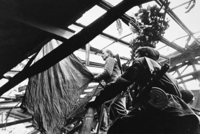 Михаил Егоров и Мелитон Кантария выходят со знаменем на крышу Рейхстага. Хотя это было не первое установленное на Рейхстаге красное знамя, но именно оно стало Знаменем Победы.