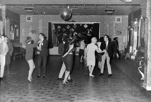 Битлз поют для 18 человек в скромном клубе городка Олдершот в декабре 1961 года. Через полтора года они станут мега-звездами.