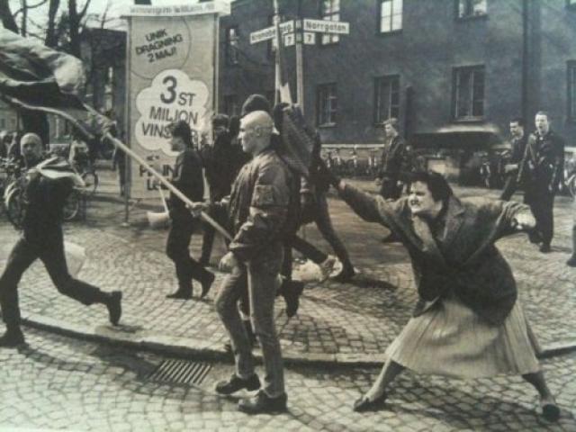 Снимок был сделан во время неонацистской демонстрации в шведском городе Växjö, апрель 1985 года. Позже стало известно, что эта женщина, будучи еще ребенком во время Второй мировой войны, смогла чудом выжить в одном из концентрационных лагерей смерти.