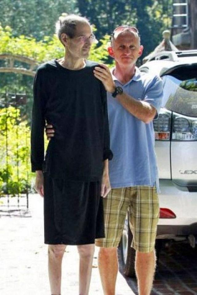 Друг помогает больному раком Стиву Джобсу дойти до машины у его дома в Калифорнии 26 августа 2011 года.