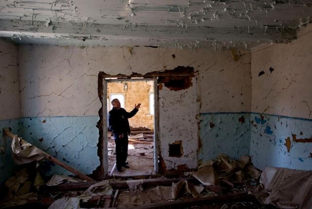 А это мужчина в своем бывшем доме в запретной зоне вокруг Чернобыля, в поселке Ломыш, на юго-востоке от Минска, 18 марта 2011 года.