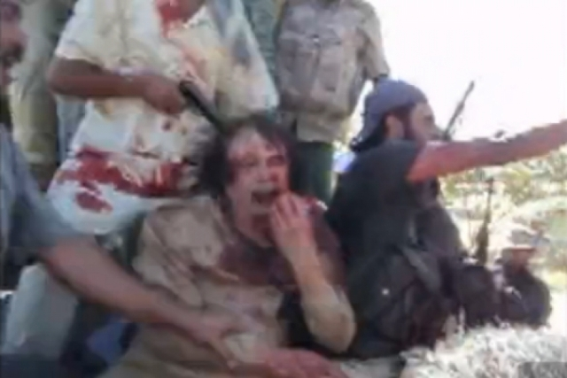 """Люди с криками """"Аллаху Акбар!"""" принялись стрелять в воздух и тыкать в полковника автоматами. Каддафи подвергся многочисленным пыткам, после чего был казнен ."""