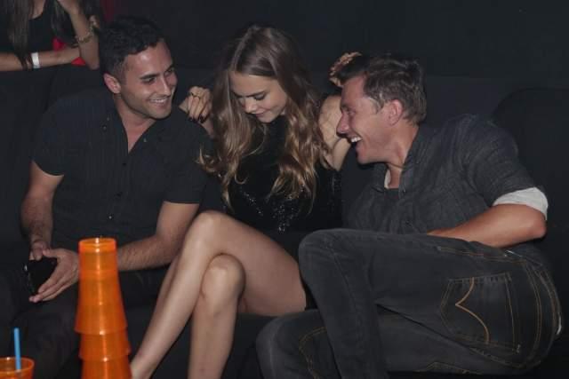 Кара Делевинь в компании сразу двух товарищей по вечеринке.