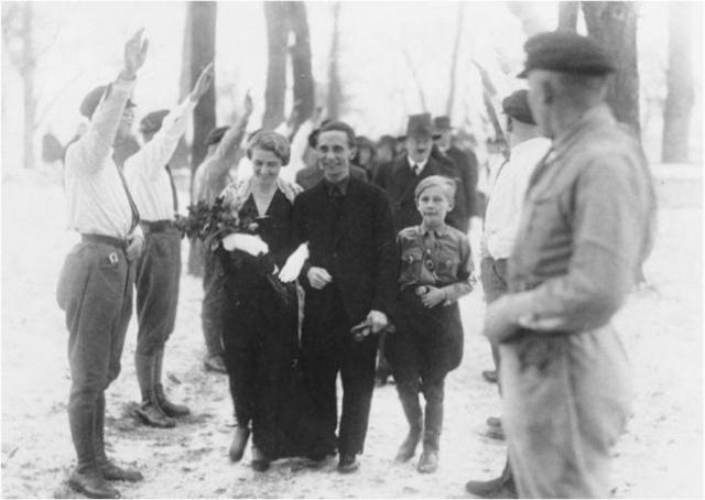 На втором плане можно рассмотреть Гитлера, ставшего гостем на свадьбе Геббельса.