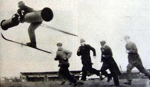 """Летун на лыжах. В 1934 года немецкая газета Berliner Illustrirte Zeitung опубликовала фотоснимок немецкого пилота Эриха Кочера, летящего по воздуху, на ногах которого были обуты лыжи, а позади - """"плавник"""". При этом он дул в некое устройство, которое держал в руках."""