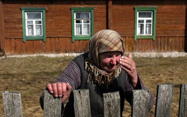 Плачущая 67-летняя Настасия Васильева у своего дома в пострадавшей от катастрофы деревне Радныя в запретной зоне, в 45 км от Чернобыльской АЭС.