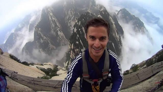 Парень взобрался на гору Хуашань в Китае и прошел по самой опасной пешей горной тропе из шатающихся досок. Селфи - подтверждение его отваги.